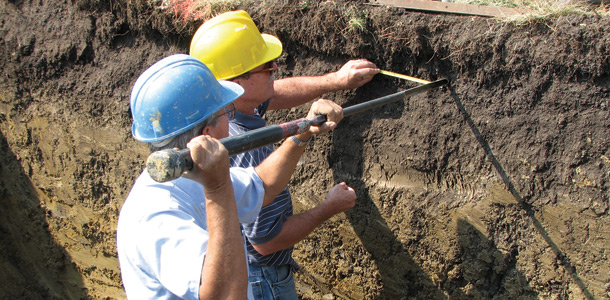Two geologists examine soil layers