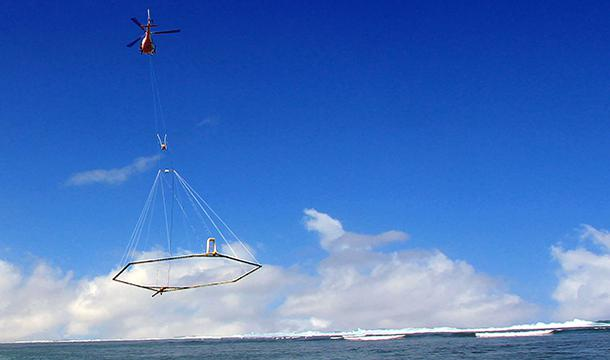 a helicopter tows an instrument array over the surface