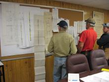 From left to right - John Nelson from ISGS, Phil Ames from Peabody Energy, and Scott Elrick from ISGS discuss a series of geologic and geophysical logs.