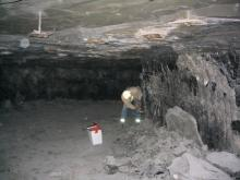 """John Nelson, in the mine and examining the coal """"rib"""". In the """"roof"""" you can see """"roof bolts"""", which are used to stabilize the roof rock and keep it from collapsing into the area from which the coal has been removed. The roof rock and coal """"rib"""" have been sprayed with limestone rock dust, used to help stop explosions from propagating in the mine. This is what causes many of the walls of the mine to appear white in color. It looks like John remembered his lunch."""