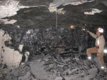 Scott Elrick, in a mine in Illinois, examining a few thin stringers of coal above the main coal seam. Part of the 'rib' or wall of the passageway has come down, allowing us to see the black and shiny nature of the coal seam and the dull dark gray of the roof shale normally hidden by the limestone rock dust.